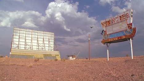 Time-lapse-of-clouds-passing-over-an-abandoned-drive-in-sign-and-screen