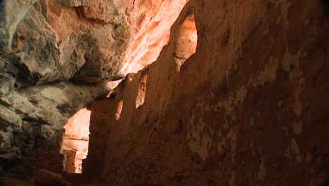 A-woman-walks-through-an-ancient-Native-American-Indian-cliff-dwelling