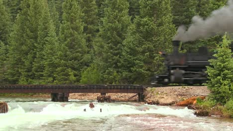 A-beautiful-shot-of-a-steam-train-crossing-a-bridge-over-a-roaring-river-in-the-Rocky-Mountains