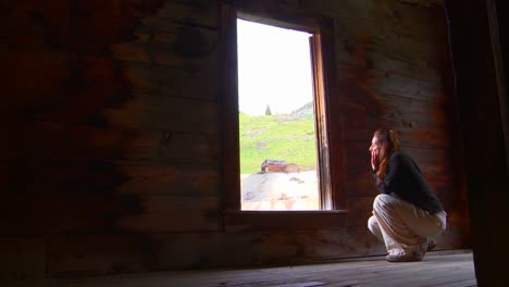 A-woman-sits-in-an-abandoned-house-looking-out-the-window