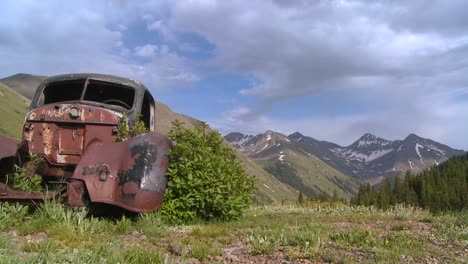 Beautiful-time-lapse-traveling-shot-across-Rocky-Mountains-with-old-abandoned-car-in-foreground