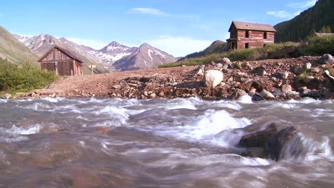 Traveling-shot-along-a-river-with-Colorado-ghost-town-background