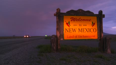 A-roadside-sign-welcomes-visitors-to-New-Mexico-as-cars-pass-at-dusk