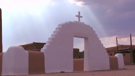 A-Christian-cross-glows-against-a-heavenly-sky-at-the-Taos-pueblo
