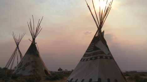 Indian-teepees-stand-in-a-native-american-encampment-at-sunset