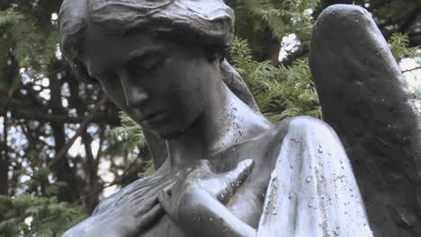 A-statue-of-an-angel-stands-over-a-grave-in-a-cemetery
