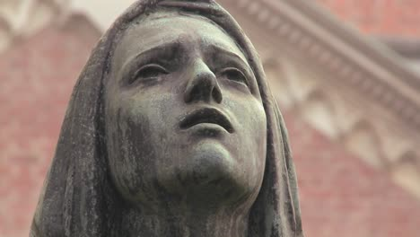 A-statue-of-a-woman-weeping-in-a-cemetery-or-church