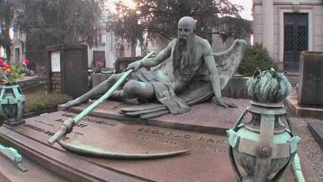The-grim-reaper-sits-on-a-tomb-in-a-graveyard-with-his-scythe-1