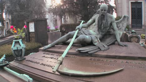 The-grim-reaper-sits-on-a-tomb-in-a-graveyard-with-his-scythe-2
