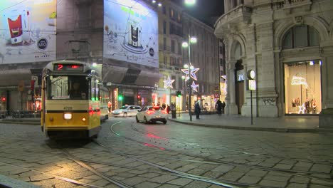 A-trolley-passes-at-night-on-a-street-in-Milan-Italy
