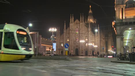 A-trolley-passes-at-night-on-a-street-in-front-of-the-Duomo-cathedral-in-Milan-Italy