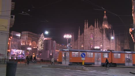 A-trolley-passes-at-night-on-a-street-in-front-of-the-Duomo-cathedral-in-Milan-Italy-1