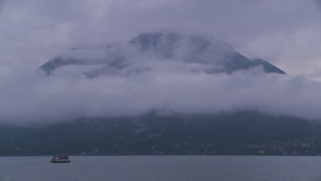 A-morning-ferry-boat-on-Lake-Como-Italy-cruises-past-mountains-in-the-fog
