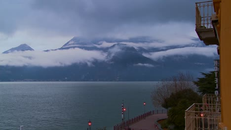 Fog-rolls-in-over-the-mountains-of-Lake-Como-Italy-with-a-hotel-balcony-naarby