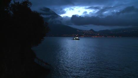 Un-Barco-Distante-Cruza-Un-Lago-Oscuro-Por-La-Noche