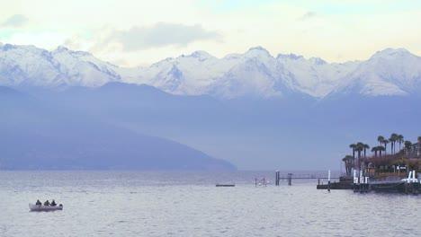 Un-Barco-De-Pesca-Flota-Ante-Un-Hermoso-Y-Pequeño-Pueblo-Italiano-De-Bellagio-A-Orillas-Del-Lago-De-Como-Con-Los-Alpes-Italianos-En-Segundo-Plano-
