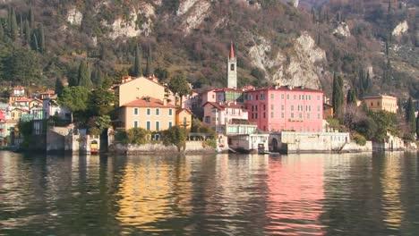 Pov-Desde-Un-Barco-De-Las-Orillas-Del-Lago-De-Como-Con-La-Ciudad-De-Varenna-Y-Los-Alpes-Italianos-Al-Fondo-1