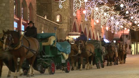 A-horse-drawn-carriage-makes-its-way-down-a-snowy-street-in-wintertime