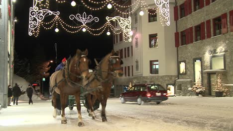 A-horse-drawn-carriage-makes-its-way-down-a-snowy-street-in-wintertime-1