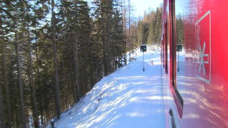A-POV-shot-from-the-side-of-a-train-as-it-moves-through-a-snowy-landscape