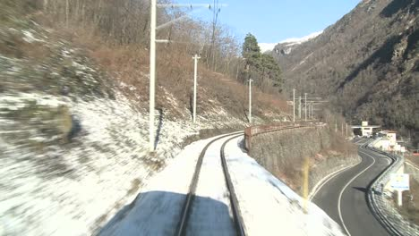 A-time-lapse-POV-shot-from-the-front-of-a-train-moving-through-a-mountainous-region