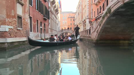 A-gondola-is-rowed-through-a-quiet-canal-in-Venice-Italy