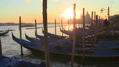 A-beautiful-shot-of-the-sun-setting-behind-rows-of-gondolas-in-Venice-Italy