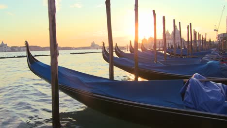 A-beautiful-shot-of-the-sun-setting-behind-rows-of-gondolas-in-Venice-Italy-1