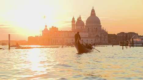 A-gondola-is-rowed-by-a-gondolier-in-front-of-the-setting-sun-in-romantic-Venice-Italy