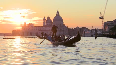 A-gondola-is-rowed-by-a-gondolier-in-front-of-the-setting-sun-in-romantic-Venice-Italy-1