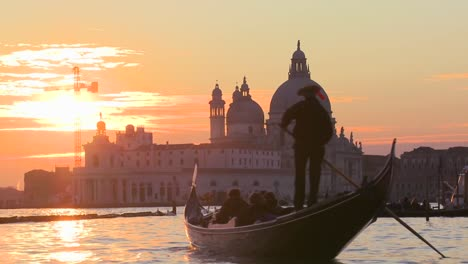 A-gondola-is-rowed-by-a-gondolier-in-front-of-the-setting-sun-in-romantic-Venice-Italy-2