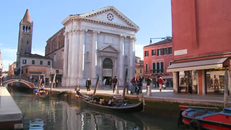 Pedestrians-and-boats-on-a-quiet-canal-in-Venice-Italy