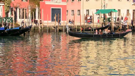 A-gondola-is-rowed-across-beautiful-colorful-water-in-Venice-Italy