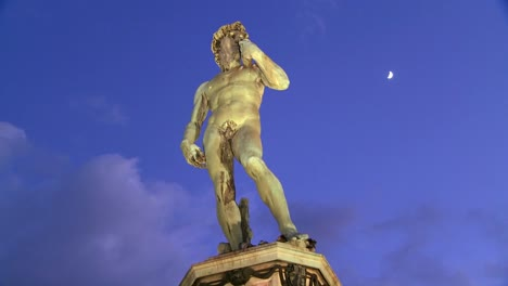 Time-lapse-of-State-of-David-at-dusk-in-Florence-Italy-with-moon-in-background