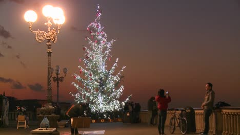 A-Christmas-tree-against-the-dusk-with-pedestrians