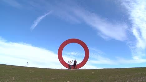Dos-Personas-Se-Sientan-En-Una-Escultura-De-La-Letra-O-Contra-Un-Cielo-Abierto