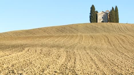 Un-Disparo-A-Través-De-Los-Campos-De-Toscana-Italia-Hasta-Una-Casa-De-Campo-O-Iglesia-Lejana