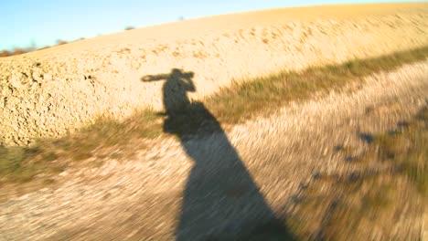 The-shadow-of-a-filmmaker-walking-along-a-dirt-road