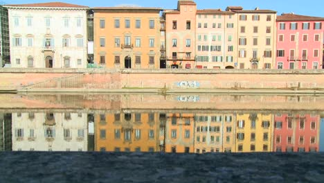 Buildings-line-and-are-reflected-in-a-symmetrical-canal-in-Pisa-Italy