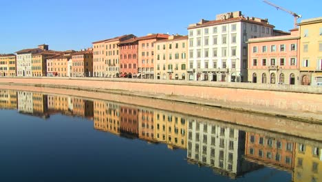 Buildings-line-and-are-reflected-in-a-symmetrical-canal-in-Pisa-Italy-1