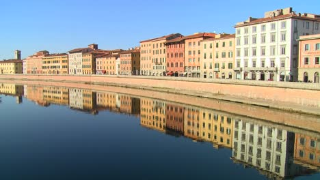 Buildings-line-and-are-reflected-in-a-symmetrical-canal-in-Pisa-Italy-2