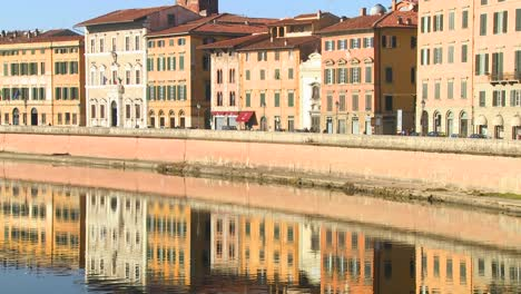 Buildings-line-and-are-reflected-in-a-symmetrical-canal-in-Pisa-Italy-3
