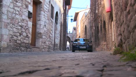 A-new-BMW-drives-down-a-narrow-alley-in-Assisi-Italy