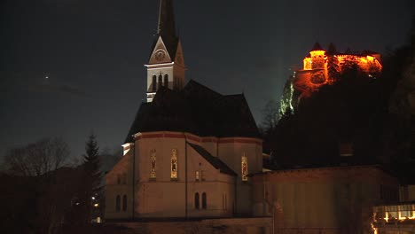 A-church-and-distant-medieval-castle-at-night-at-Lake-Bled-Slovenia