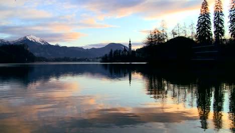 A-small-church-on-a-distant-island-at-dawn-at-Lake-Bled-Slovenia