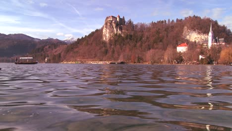 A-boat-passes-a-beautiful-medieval-castle-and-church-on-the-shores-of-Lake-Bled-Slovenia