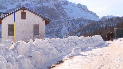 Una-Pareja-De-Ancianos-Camina-Por-Una-Carretera-Cubierta-De-Nieve-En-Los-Alpes-Suizos