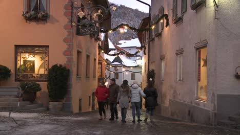 People-walk-in-a-snowbound-Tyrolean-village-in-the-Alps-in-Austria-Switzerland-Italy-Slovenia-or-an-Eastern-European-country