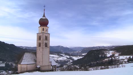 Time-lapse-clouds-over-an-Eastern-church-in-a-snowbound-Tyrolean-village-in-the-Alps-in-Austria-Switzerland-Italy-Slovenia-or-an-Eastern-European-country