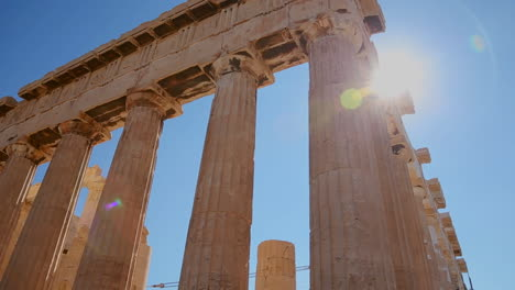 Low-angle-pan-of-the-columns-of-the-Acropolis-and-Parthenon-on-the-hilltop-in-Athens-Greece